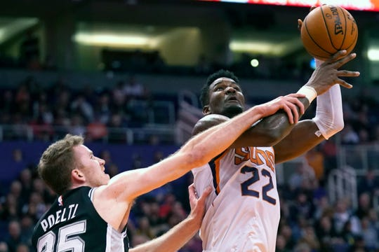 Phoenix Suns center Deandre Ayton gets fouled by San Antonio Spurs center Jakob Poeltl (25) during the second half of an NBA basketball game Monday, Jan. 20, 2020, in Phoenix. San Antonio won 120-118. (AP Photo/Rick Scuteri)