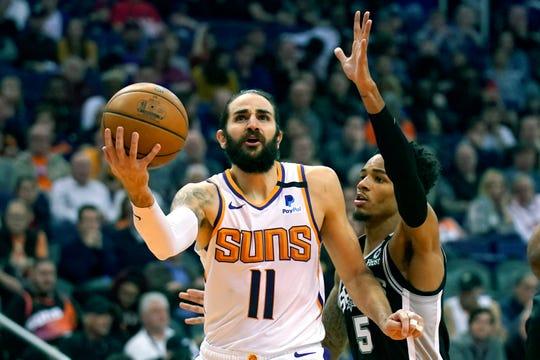 Phoenix Suns guard Ricky Rubio (11) drives by San Antonio Spurs guard Dejounte Murray during the second half of an NBA basketball game Monday, Jan. 20, 2020, in Phoenix. San Antonio won 120-118. (AP Photo/Rick Scuteri)