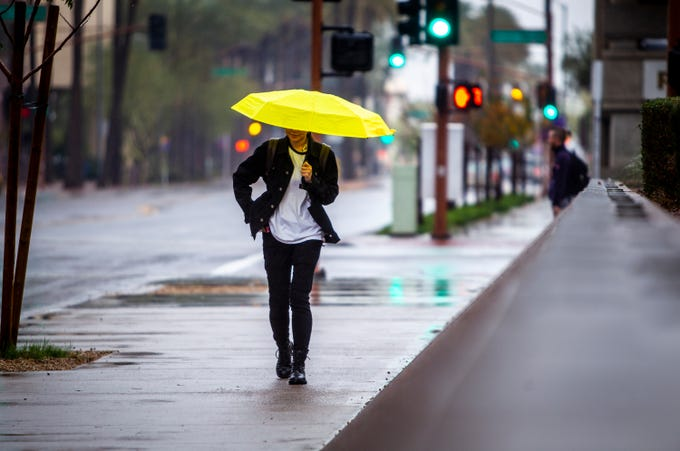 A woman walks with an umbrella protecting herself from the rain in downtown Phoenix during a rainstorm on Tuesday, Jan. 21, 2020.