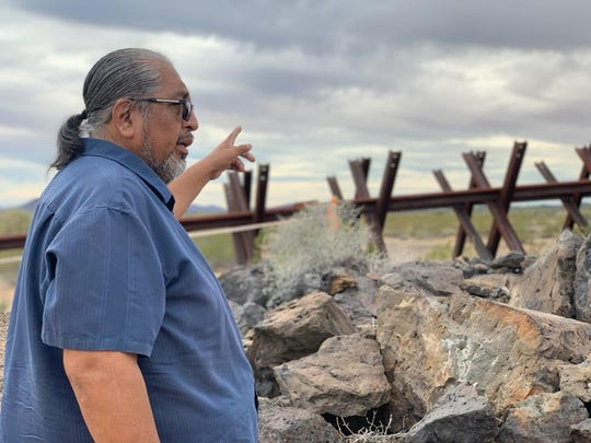 Tohono O'Odham Chairman Ned Norris points to other O'Odham archaeological sites found on the other side of the Normandy-style vehicle barriers in Mexico on Jan. 20, 2020.