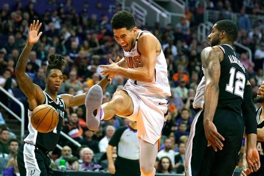 Phoenix Suns guard Devin Booker loses control of the ball between San Antonio Spurs guard Lonnie Walker IV (1) and LaMarcus Aldridge (12) during the second half of an NBA basketball game Monday, Jan. 20, 2020, in Phoenix. San Antonio won 120-118. (AP Photo/Rick Scuteri)
