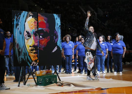 Local speed painter Alejandro Ruiz waves after creating a portrait of King Jr. while the Pilgrim Rest Baptist Church choir sings during the halftime between the Phoenix Suns and the San Antonio Spurs January 20, 2020. The completed MLK portrait will be gifted to the church.