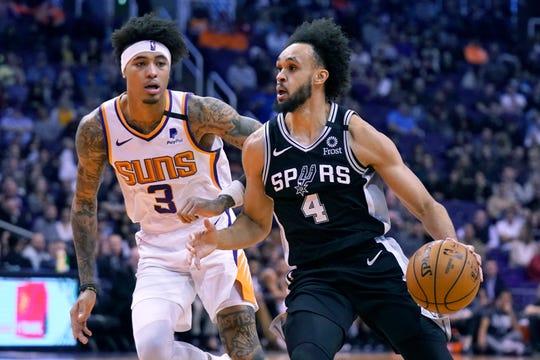 San Antonio Spurs guard Derrick White (4) drives past Phoenix Suns forward Kelly Oubre Jr. during the first half of an NBA basketball game Monday, Jan. 20, 2020, in Phoenix. (AP Photo/Rick Scuteri)