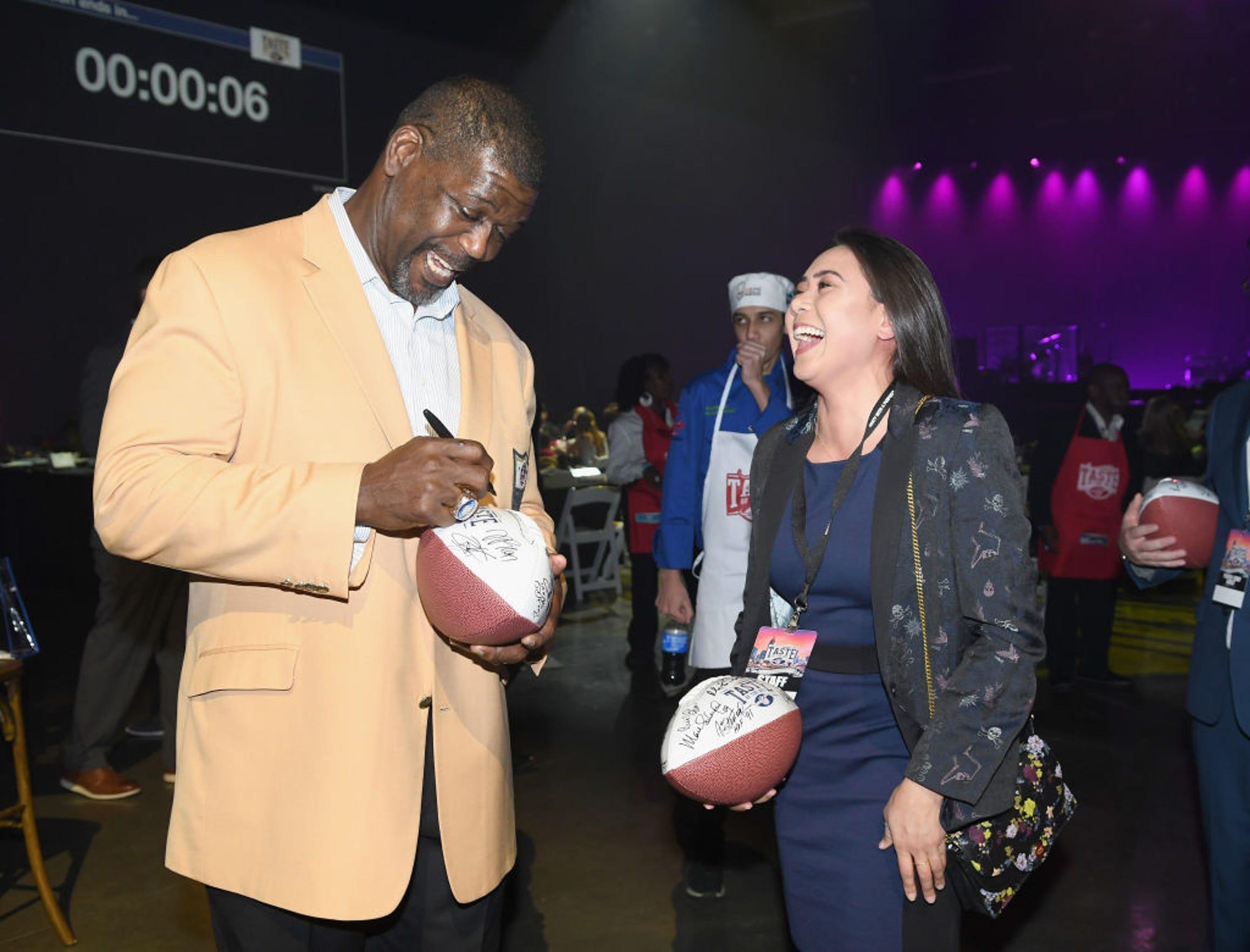 Randall McDaniel, Salón de la Fama de la NFL, firma un autógrafo a una asistente al evento.