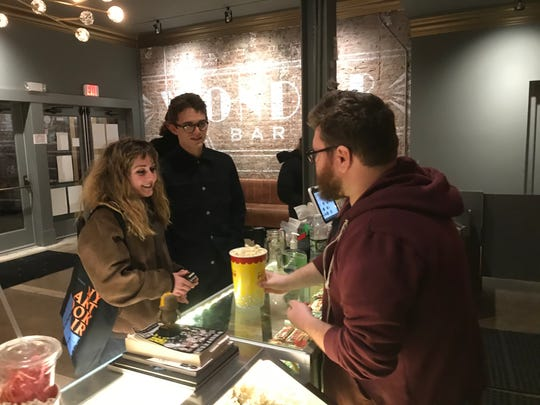 """Robby Anderson of Beacon, 28, right, serves popcorn recently to Kevin McMorrow, 22, of Wingdale, center, and his girlfriend, Isabella Convertino, 21, of Garrison, before they head in to see """"Little Women."""""""