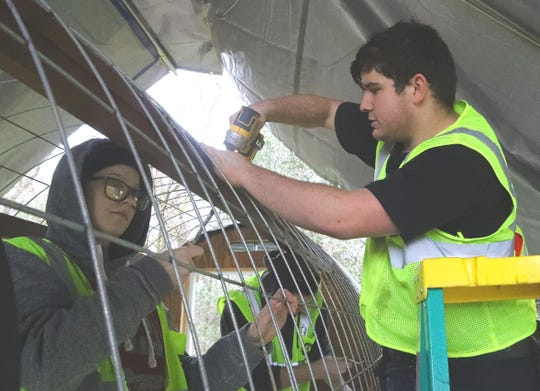 California Heritage YouthBuild Academy students Kaylah Adams, 18, left, and Jacob Wegner, 16, help construct a micro shelter at their Airport Road campus on Tuesday, Jan. 21, 2020. A Hut Crew from Eugene, Oregon, pre-assembled parts of the structure and helped the students put it together to demonstrate an affordable option for the homeless.