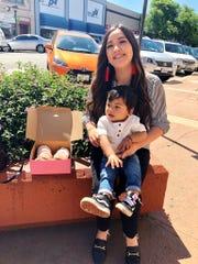 Yvette Tinoco, de 29 años, y su hijo, sentados junto a una caja llena de donas veganas de Hole Foods en el centro de Salinas, 11 de mayo de 2019