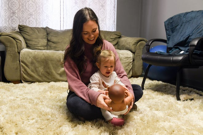 "Samantha Tully, owner of Mama Be, plays with her 1-year-old daughter, Emery, on Tuesday, Jan. 21, at her office in Sioux Falls. The doll, nicknamed ""Baby Marie,"" is used as a positioning model for Tully's breastfeeding consulting."
