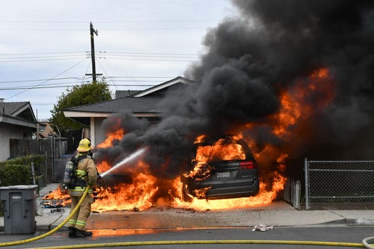 An Oxnard firefighter attacks flames engulfing two cars Monday afternoon. A woman suffered serious burn injuries, officials said.