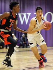 New Rochelle's Prakash Ketterhagan (4) goes up for two with Quion Burns (0) of White Plains guarding him during boys basketball game at New Rochelle High School on Jan. 21, 2020. New Rochelle defeats White Plains 73-58.