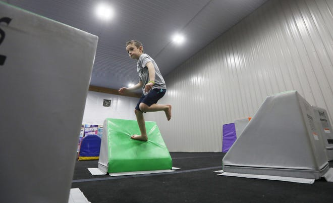Hunter Smith works his way across part of the ninja course at Champion Gymnastics and Cheer.