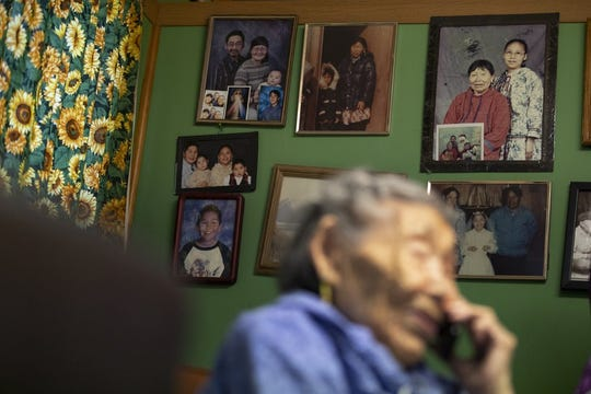 In this Monday, Jan. 20, 2020 image, family pictures hang on the wall as Lizzie Chimiugak talks on the phone at her home in Toksook Bay, Alaska.