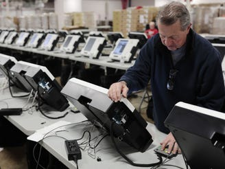 Scott Thomas, a logistics technician, prepares to boot up new voting machines as he works on Friday, February 1, 2019 at the Franklin County Board of Elections in Columbus, Ohio. The new machines eject a paper ballot with a voter's selections on it, which is then taken to a ballot counter machine at each precinct where votes are recorded.
