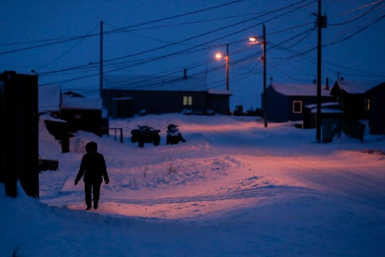 In this Jan. 20, 2020 photo, a woman walks before dawn in Toksook Bay, Alaska, a mostly Yuip'ik village on the edge of the Bering Sea. Census workers traditionally begin the official decennial count in rural Alaska when the ground is still frozen. That allows easier access before the spring melt makes many areas inaccessible to travel and residents scatter to subsistence hunting and fishing grounds.