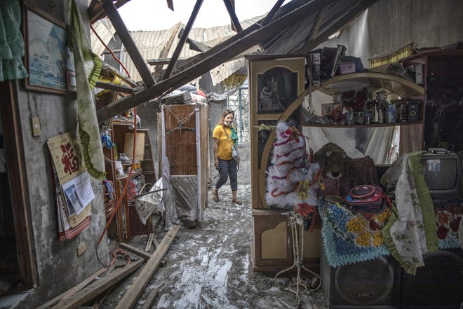 Jacquiline Bukid inside her house. Its roof collapsed due to heavy volcanic ash from Taal Volcano's eruption on Jan. 20 in the village of Buso Buso, Laurel, Batangas, Philippines.