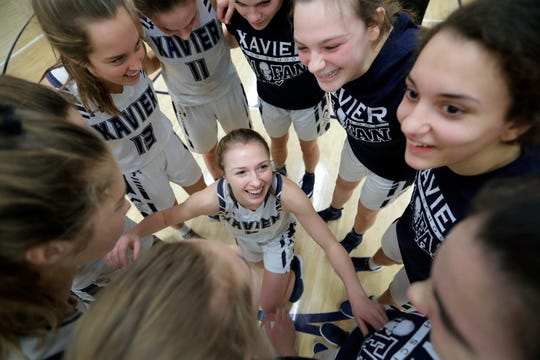 Xavier's Izzy Ballard, center, huddles up her team for a moment before playing against Menasha during a Bay Conference game Jan. 21 in Appleton.