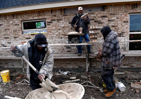 Jermaine Kanzig scoops a shovelful of mortar as Angel De Leon carries more bricks over and Candelario Jimenez (top) continues building a house wall Tuesday. The men work for Big Dawg Masonry and were building houses in the Butterfield Meadows subdivision along U.S. Highway 277.