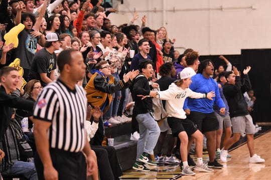 The Abilene High student section celebrates a four-point play by Jalen McGee during the first half of the 56-50 win against Euless Trinity at Eagle Gym.