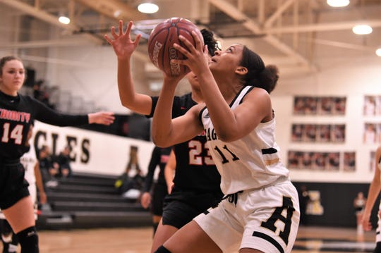 Abilene High's Destiny Potts (11) looks up at the basket for a shot in the post against Euless Trinity at Eagle Gym on Tuesday, Jan. 21, 2020. The Lady Eagles got off to a slow start in the 67-42 loss.