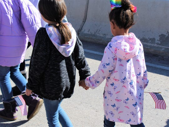 Two girls walk hand in hand across the Martin Luther King Jr. Memorial Bridge in east Abilene on Jan. 20, each carrying a U.S. flag.