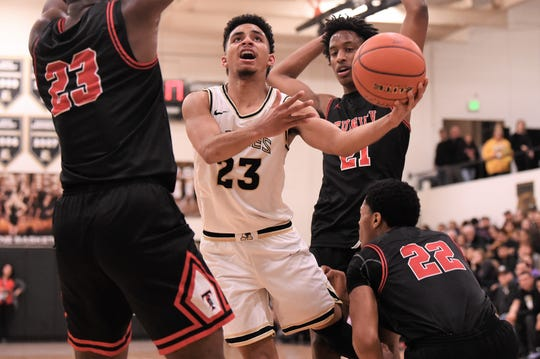 Abilene High's D.J. Modest (23) goes between a pair of Euless Trinity defenders for a shot at Eagle Gym on Tuesday, Jan. 21, 2020. Modest helped lead the Eagles to a 56-50 win with 16 points.