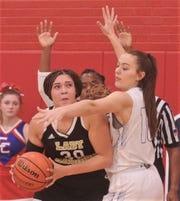 Cooper's Brianna Garcia, right, and a teammate defend against Wichita Falls Rider's Addison Self (30).