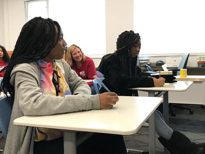 Eighth graders Ana'ya Harper (right) and Eniyah Lee-Blair (left) discuss their school and life experiences as AMS Principal April Dockery (middle) watches on.