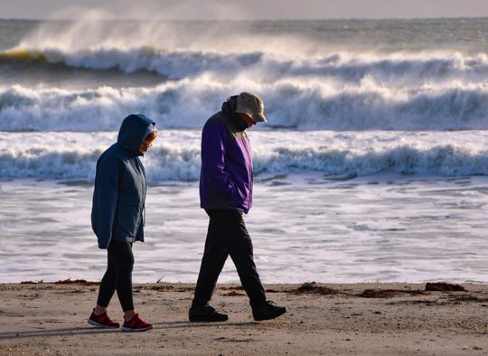 Paula and Sam Barone, on vacation from Ohio, weren't going to let temperatures in the low 40s and a wind chill in the 20s stop them from a morning walk on Cocoa Beach looking for seashells Jan. 22, 2020.