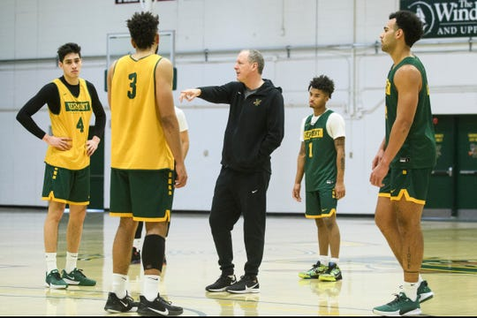 Vermont's Anthony Lamb (3), Robin Duncan (4) and Aaron Deloney (1) listen to head coach John Becker's instructions during the Vermont Catamounts men's basketball practice at Patrick Gym on Tuesday January 21, 2020 in Burlington, Vermont.