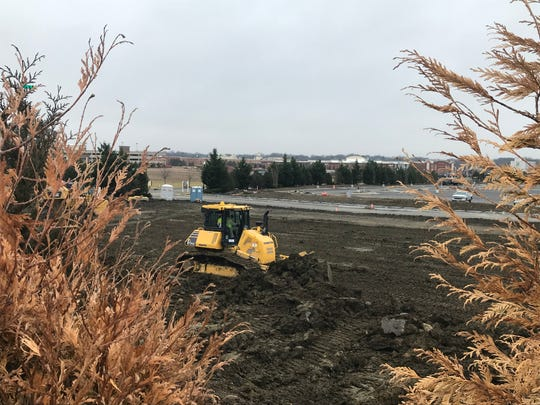 An earthmover prepares a parcel that will hold stores for Costco, Duluth Trading Co. and Wren Kitchens at the former site of Garden State Park racetrack in Cherry Hill.