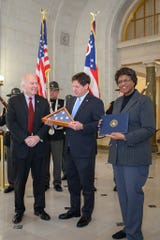 Common Pleas Judge Charles Kubicki, at center, accepts the flag that was flown over the U.S. Capitol for the 100th anniversary of the Hamilton County Courthouse from U.S. Rep. Steve Chabot on Wednesday, Jan. 22, 2020. At right is Common Pleas Judge Melba Marsh.