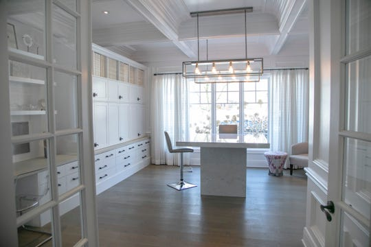"""The main floor bonus room, at 24 feet long, has been made into an office and project space with a built-in desk, a wall of cupboards and a long high-top table. """"It's a universal room. We all used it,"""" the owner said."""