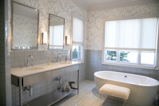 A specially built piece of stainless steel holds dual sinks in the owners' bath. The bath also has a large vanity and storage area and a large steam shower.