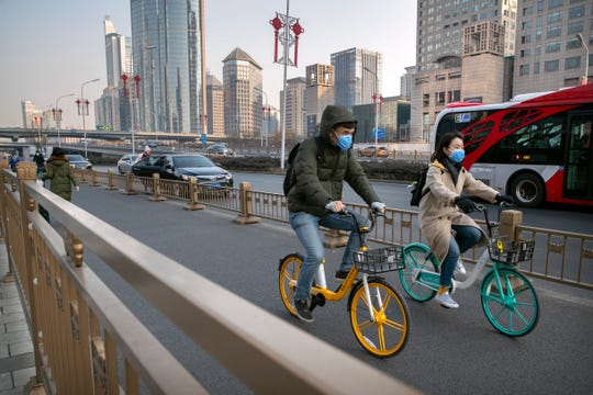 A couple wear face masks as they ride along a street in Beijing, Wednesday.