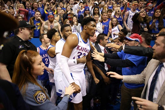 Kansas' David McCormack (33) is held back by teammate Isaiah Moss during a brawl following a game against rival Kansas State Tuedsay at Allen Fieldhouse in Lawrence, Kan.. Kansas won, 81-60.