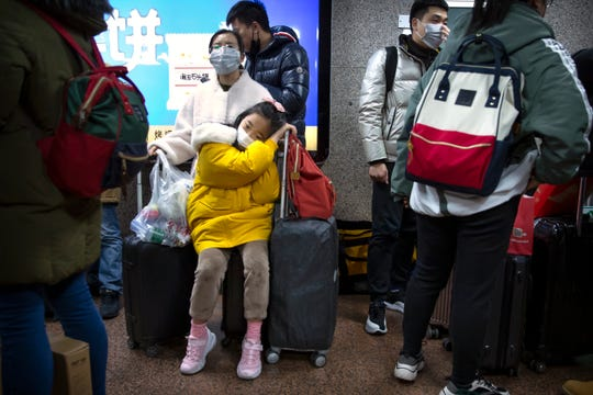 A girl wears a face mask as she sits on a suitcase at the Beijing West Railway Station in Beijing, Tuesday, Jan. 21, 2020.