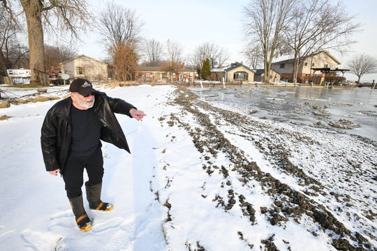 Harrison Township resident Joe Solomon points out a ridge of substance that has clogged the beach in front of his Lake St. Clair home.