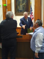 Lee County Commissioner Frank Mann offers hand to developer Joseph Cameratta after commission zoning session as Cameratta Companies President Roy Blacksmith looks on. After years of skepticism, Mann praised the policy giving Cameratta the right to build more units in exchange for environmental improvements.