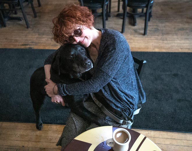 "Sylvia Bowersox gives her service dog Timothy a hug at Luna Cafe and Roastery in De Pere. She's among the veterans featured in ""To Be of Service,"" the Netflix documentary about how service dogs help veterans with PTSD."