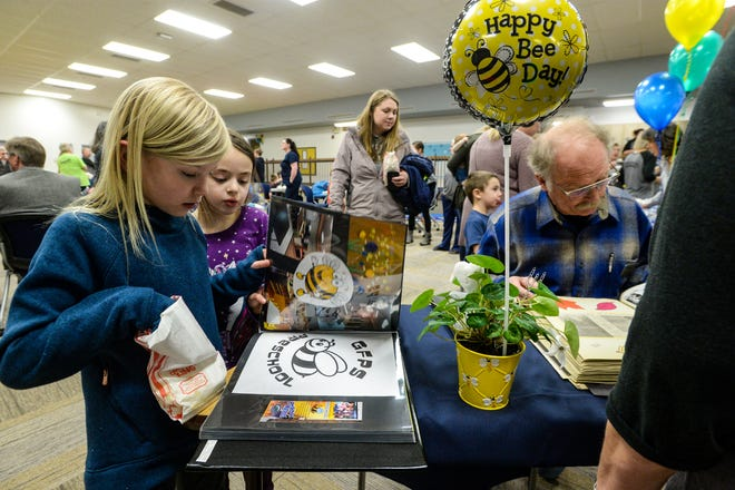 Kinly Lawrence, age 8, left, and Kaydence Gervais, age 7, look through a photo album scrap book documenting the GFPS Preschool's  first 10 years during a 10th anniversary celebration on Wednesday.