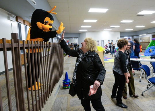 Sue Warren high-fives Buzzy, the GFPS Preschool mascot, during the preschool's 10th anniversary celebration on Wednesday afternooon.
