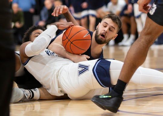 Villanova guard Justin Moore (5) and Butler forward Bryce Golden (33) scramble for a loose ball during the first half of an NCAA college basketball game, Tuesday, Jan. 21, 2020, in Villanova, Pa.