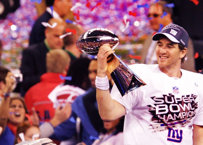 FILE -- Eli Manning, now a two-time Super Bowl champion, holds up the Vince Lombardi Trophy after he was named the MVP of Super Bowl XLVI.