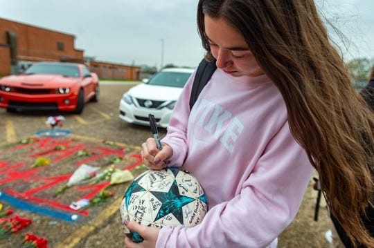 Katelyn Boudreaux signs a soccer ball at the parking lot memorial created by friends and students at Comeaux High School for 17-year-old Matthew Carter.  Wednesday, Jan. 22, 2020.