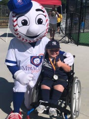 Henry Hinson poses with Miracle League of Louisville mascot Homer.