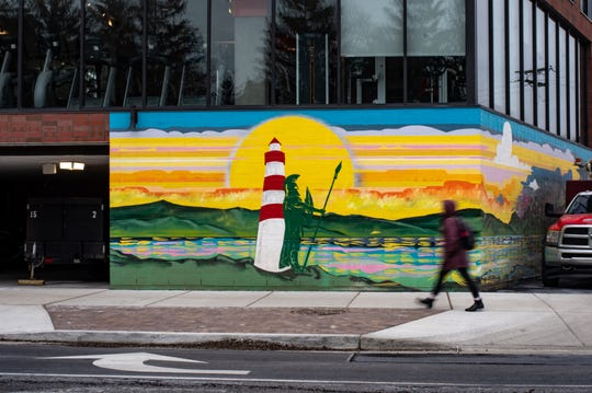 A woman walks past a mural created by artist Joe Miller on the southwest corner of The Hub in East Lansing, Thursday, Jan. 16, 2020.