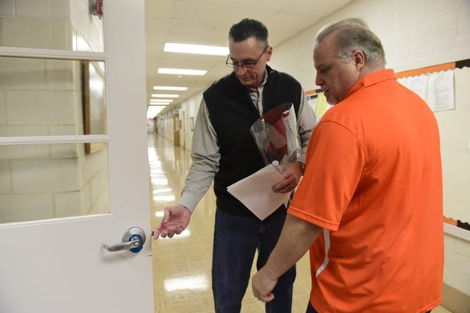 Bob Booth, left, operations manager for Mansfield City Schools, shows Chris Elswick, a member of the school board, how easily the Rapid Barricade locking system works.