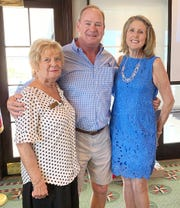 Program co-chair Sue Winje and Betsy Wohltman welcome Sam Young.