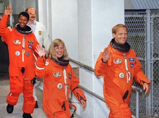 STS-47 Mission Specialists Mae Jemison, left, Jan Davis, center, and Payload Commander Mark Lee wave to photographers as they leave the operations and checkout building on the way to launch pad 39-B at Kennedy Space Center, Fla., Sept. 12, 1992. Jemison is the first black woman to ride on the shuttle and Davis and Lee are the first married couple to fly together.