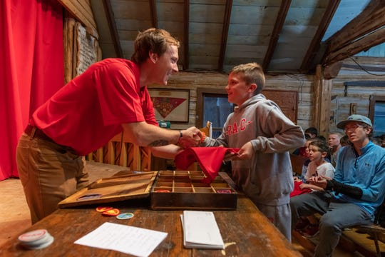 Eric Roche (left) hands a scarf to a camper at Red Arrow Camp in 2019. Every camper uses the scarf to display emblems they earn at camp over the seven-week summer session.